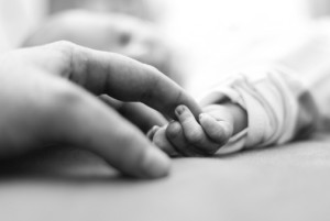 baby reaching for father's finger